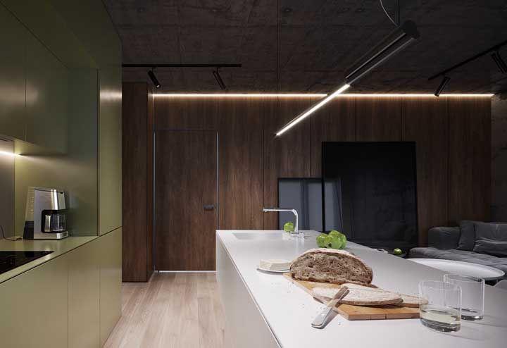 Degradê de tons que começa pelo mais escuro no teto de cimento queimado, passa pela parede de madeira escura e termina no piso de madeira clara