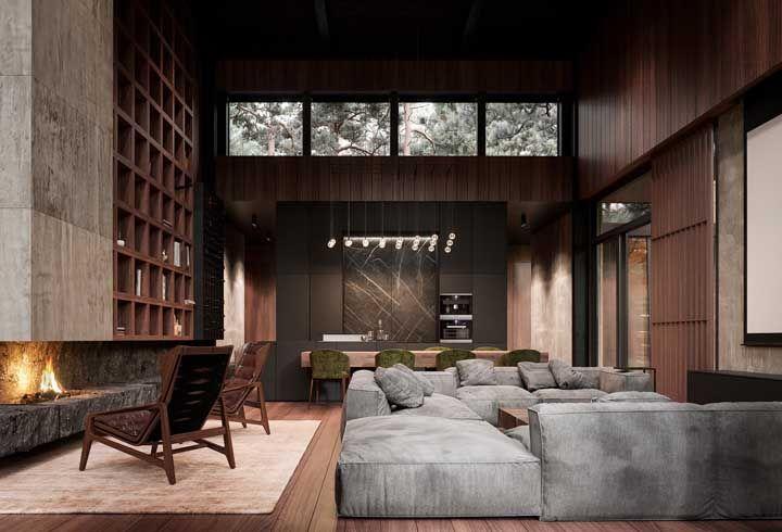 A casa de pé direito alto não hesitou em usar madeira escura em todas as paredes