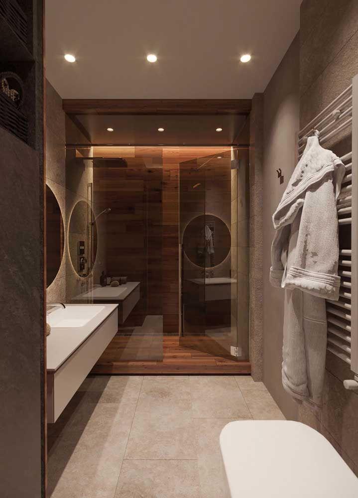 Para valorizar o uso da madeira, esse banheiro contou com a ajuda de uma iluminação direcionada