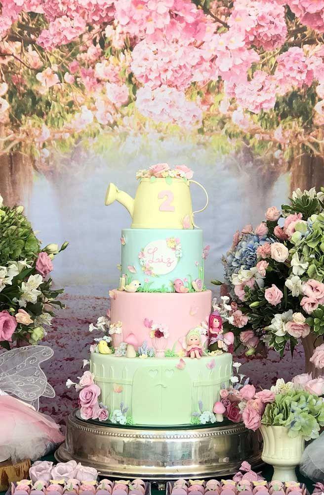Já aqui a ideia foi fazer um bolo de andar com pasta americana decorado com fadas, flores e passarinhos; destaque para o regador no topo do bolo