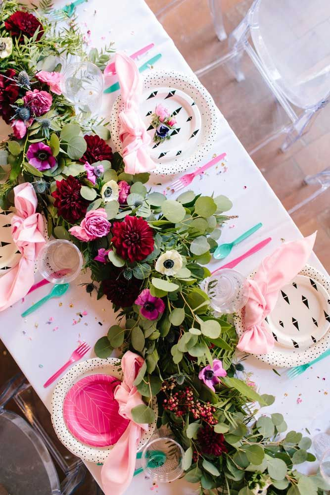 Um arranjo florido ocupando todo o centro da mesa