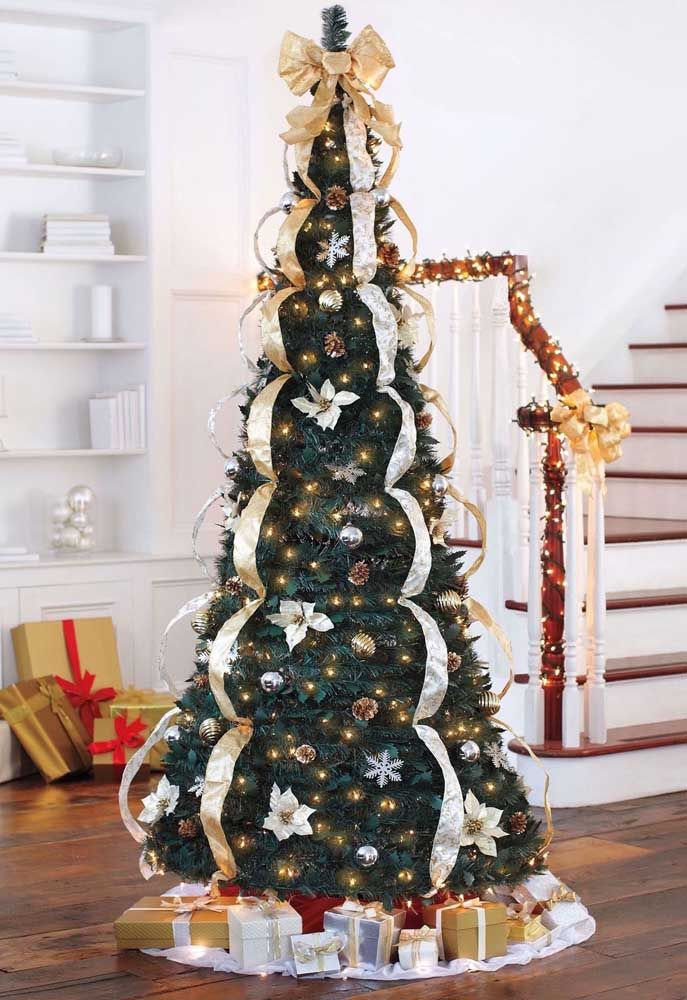 Do topo dessa árvore descem fitas douradas