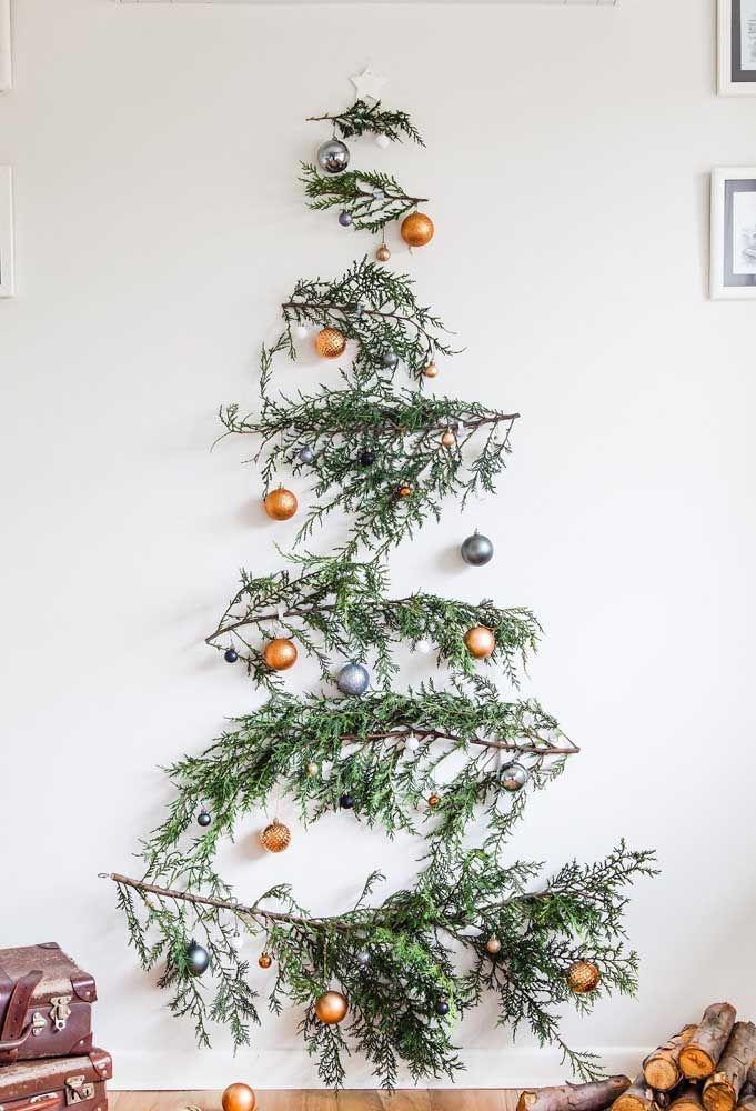 Não é por falta de espaço que você vai deixar de ter uma árvore de natal; a proposta aqui é montá-la na parede, ideia genial não é mesmo?