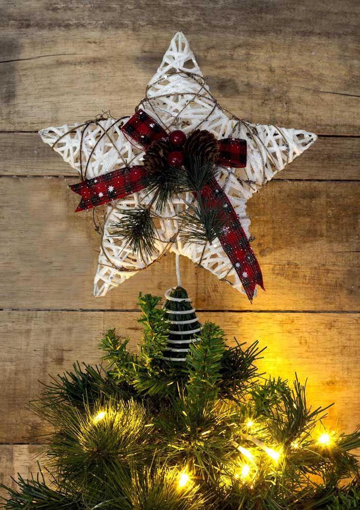 Estrela de natal feita com barbante e decorada com fita e pinhas