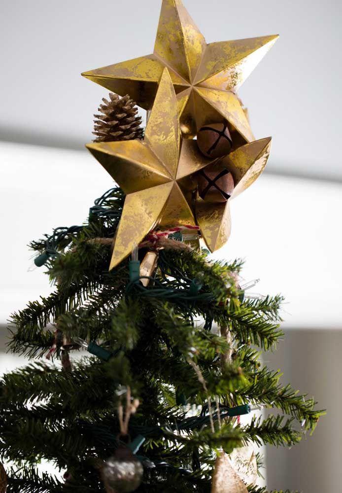 Estrela de papel com pinhas no topo da árvore