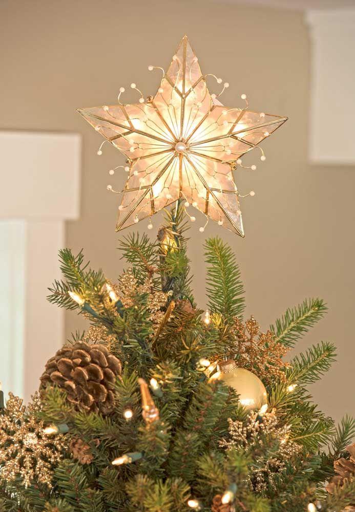Estrela de natal dourada e iluminada para combinar com os arranjos da árvore