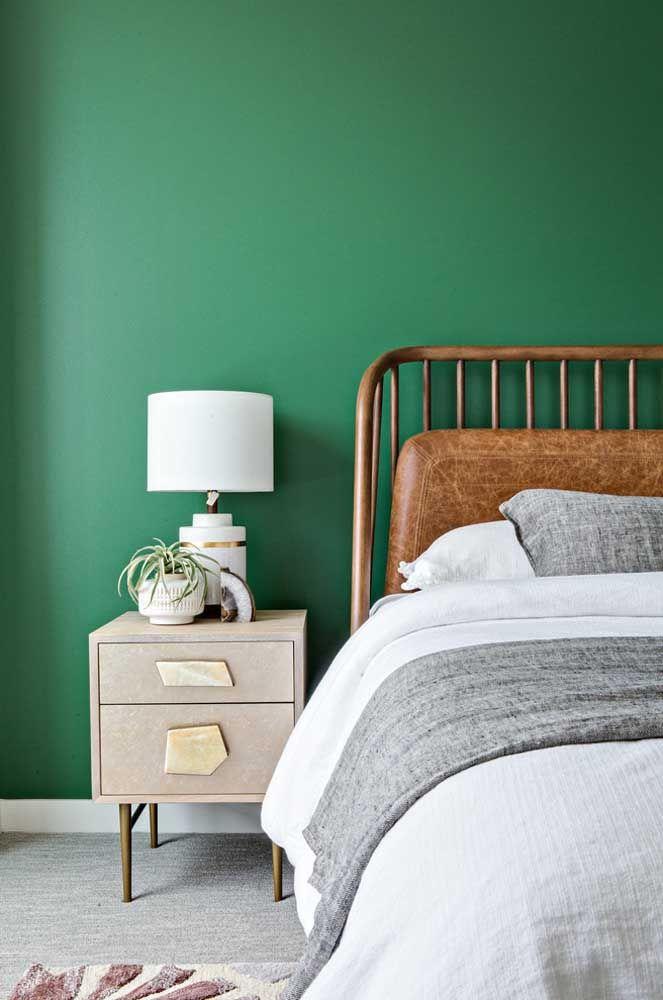 O quarto de influências marcantes – parede verde e cabeceira de couro – investiu em um criado-mudo retrô com puxadores modernos