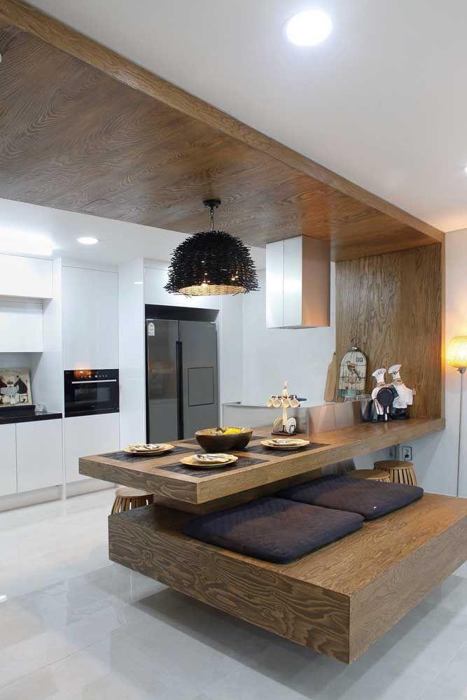 O balcão da cozinha se estende e forma um banco para acomodar quem precisa de uma refeição rápida