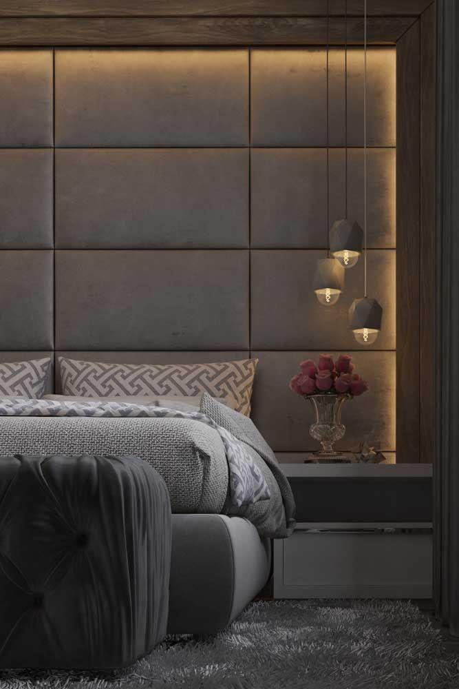 Os tons de cinza predominam na decoração desse quarto de casal; a iluminação indireta na parede e a cabeceira estofada garantem o conforto e o aconchego necessários para o ambiente