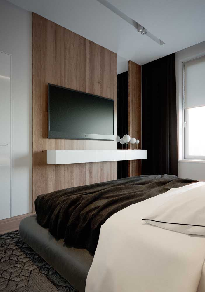 Para a TV, um painel de madeira; a prateleira suspensa fica à disposição de pequenos objetos que o casal possa levar ao quarto