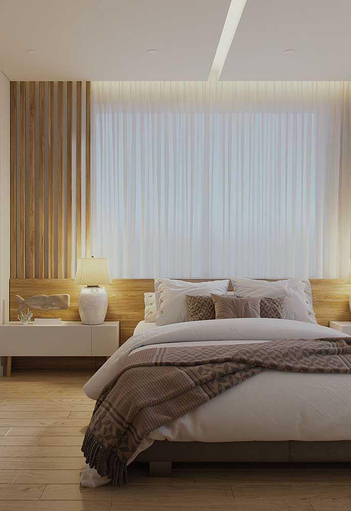 Junto à janela, a cabeceira dessa cama se completa com a cortina de voil branco