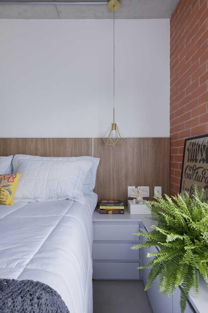 Um pouco de tudo nesse quarto: cimento queimado no teto, revestimento de tijolinho e painel laminado de madeira para a cabeceira da cama