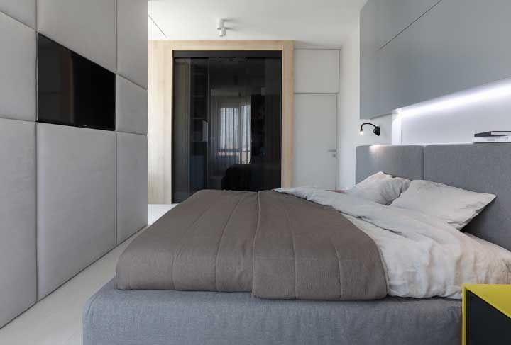 Nesse quarto de casal pequeno, o espaço entre a cama e a parede foi preenchido com o uso da TV