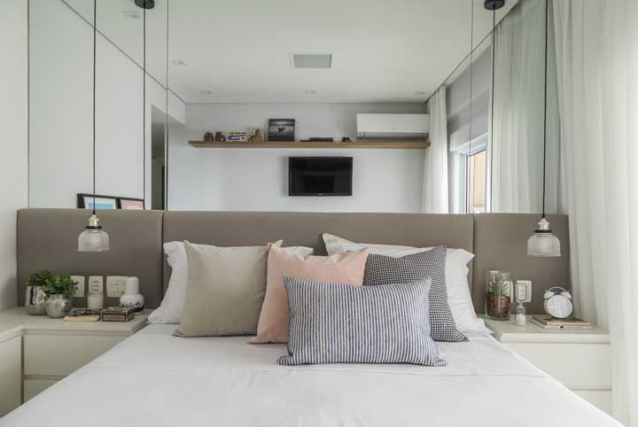 Use espelho na parede da cabeceira como truque para aumentar visualmente o quarto do casal