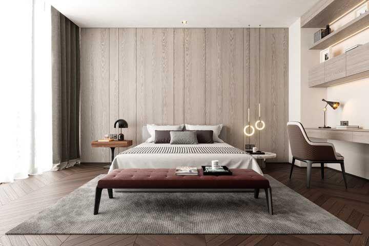 O recamier de tom vermelho queimado na base da cama é o charme desse quarto grande de casal