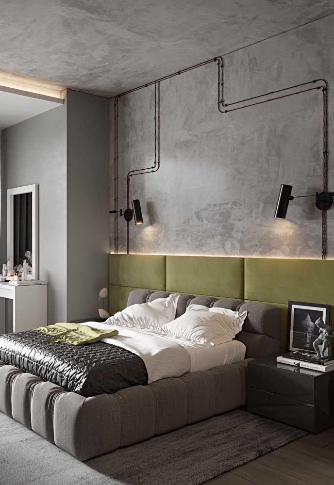 Nesse quarto de casal, a influência do estilo industrial é visível; a cabeceira amarela e iluminada aquece o ambiente