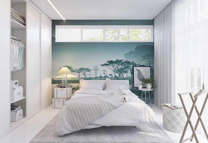 Janelas altas para reforçar a iluminação natural e um papel de parede alegre de tons azuis e verdes para contrastar o branco do quarto
