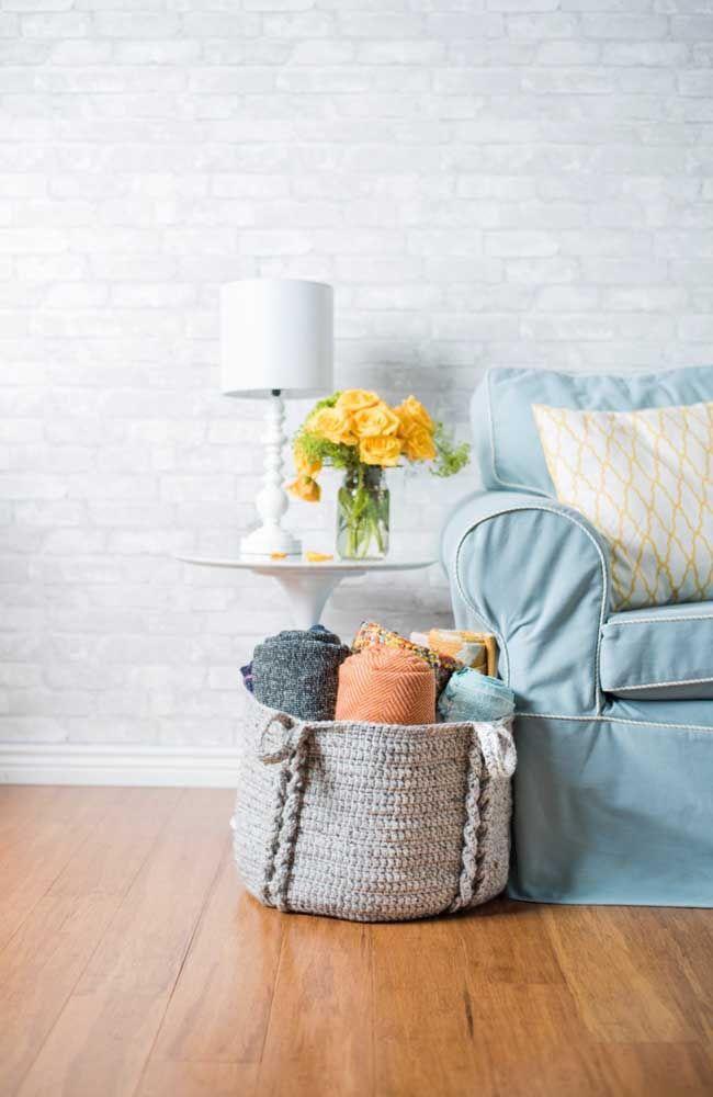 Ao lado do sofá, o cesto de crochê mantem as mantas sob controle