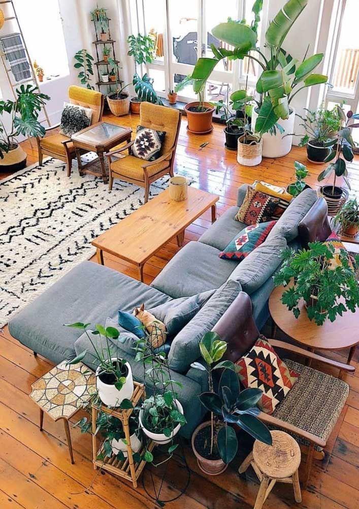 A sala de estilo boho conta com um piso de madeira impecável e lustroso