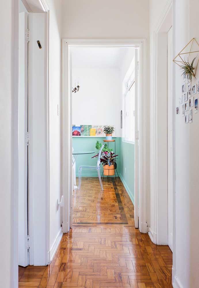 A pintura branca deixa em destaque o piso de madeira dessa casa