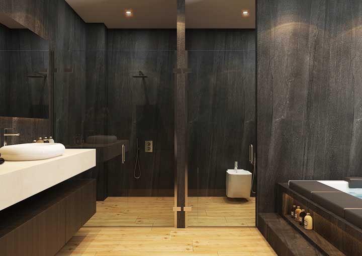 O banheiro moderno não teve medo de ousar e investiu no piso de madeira até mesmo dentro da área do banho