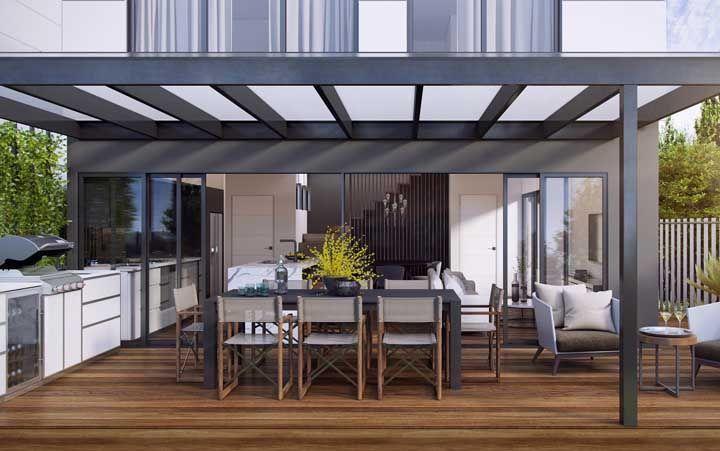 Para usar o piso de madeira na área externa e proteje-lo da chuva e do sol, a solução foi apostar no uso de um pergolado com cobertura de vidro