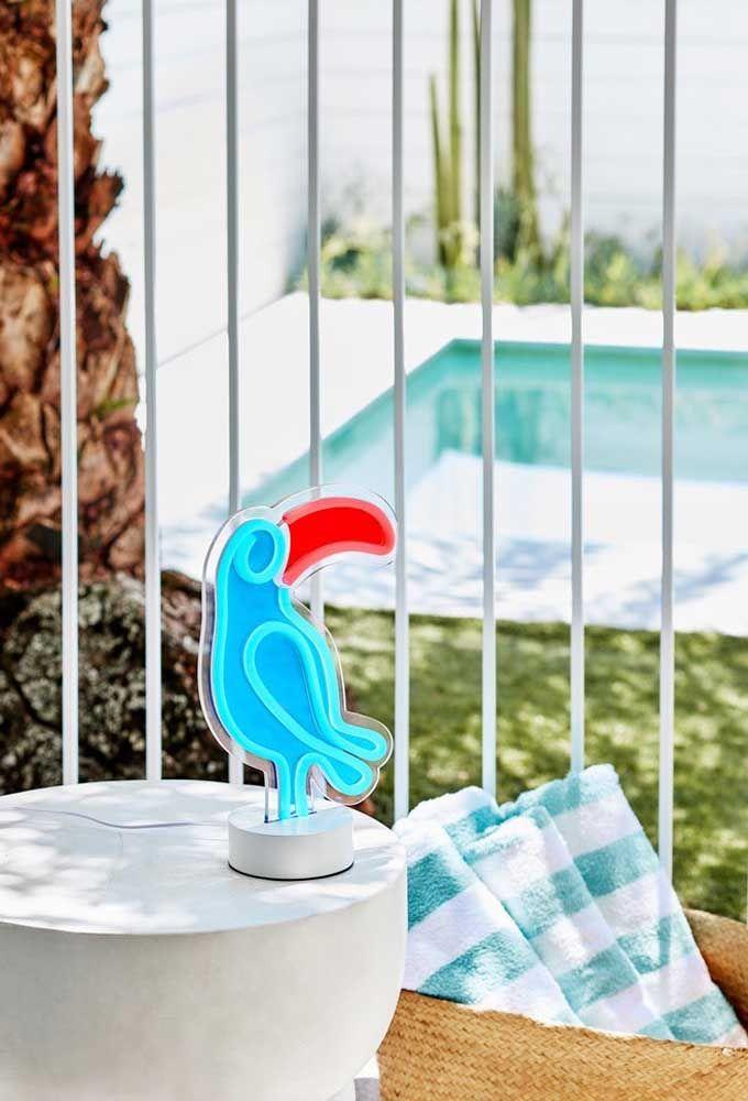 Aposte em uma luminária com formato diferente. Nesse caso, o formato é de uma arara azul. As luzes seguem as cores do bichinho