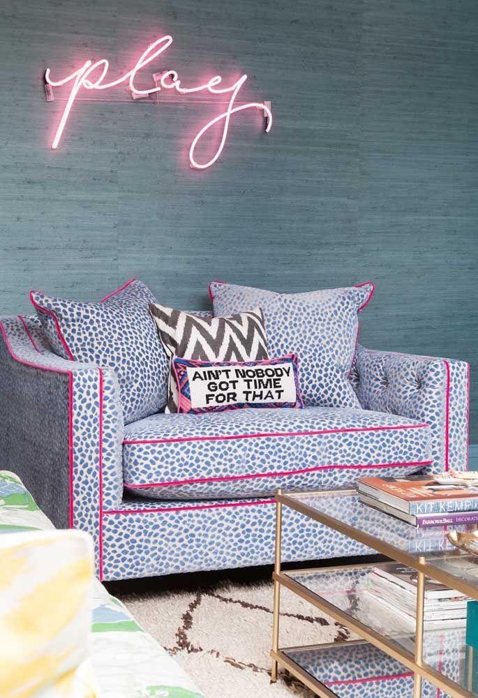 O letreiro neon no tom rosa faz uma perfeita combinação com a estampa do sofá e das almofadas
