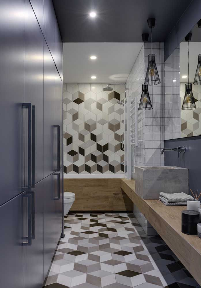 Nesse banheiro moderno e de estilo jovem, as luzes embutidas no teto formam a iluminação principal, já os pendentes reforçam a luz junto ao espelho