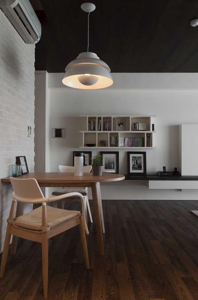 A decoração moderna desse ambiente integrado apostou no uso de uma luminária redonda sob a pequena mesa de jantar