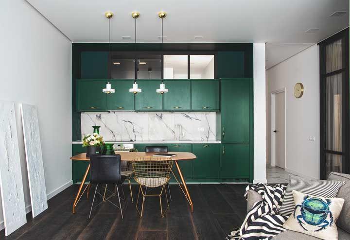 As luminárias brancas criam um bonito contraste frente ao armário de tom verde escuro