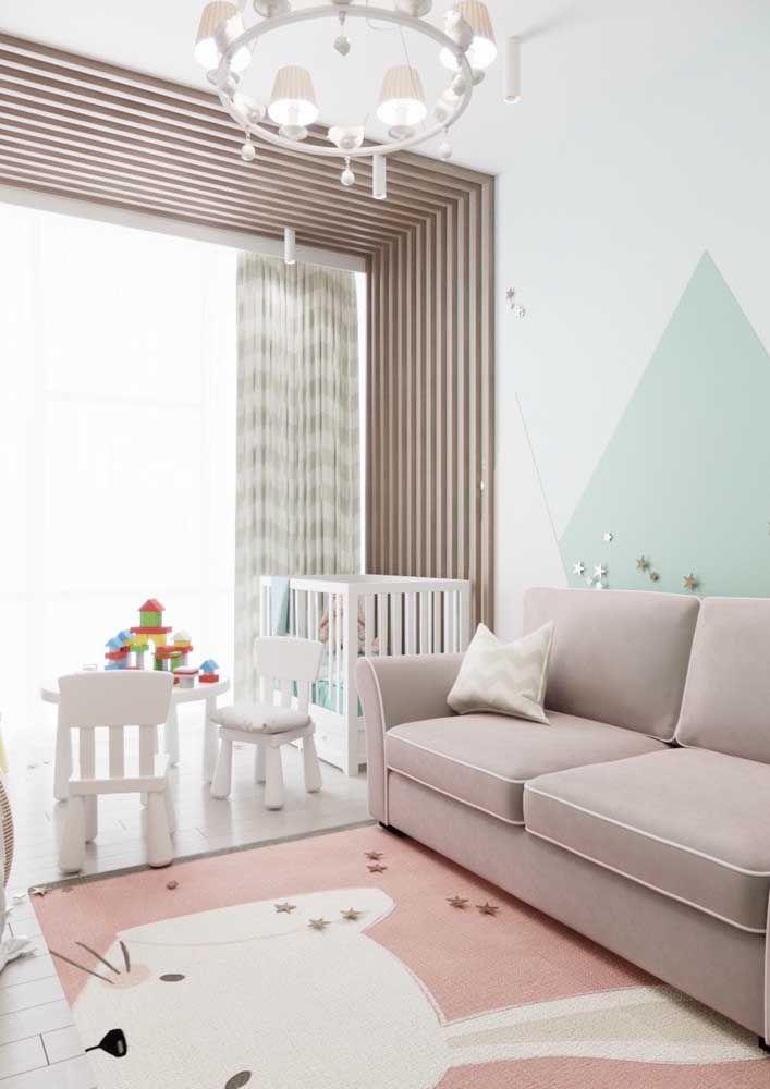 A parede geométrica e o tapete de gatinho dão o tom infantil ao quarto