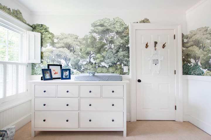 O papel de parede de floresta destacou o branco do quarto de bebê