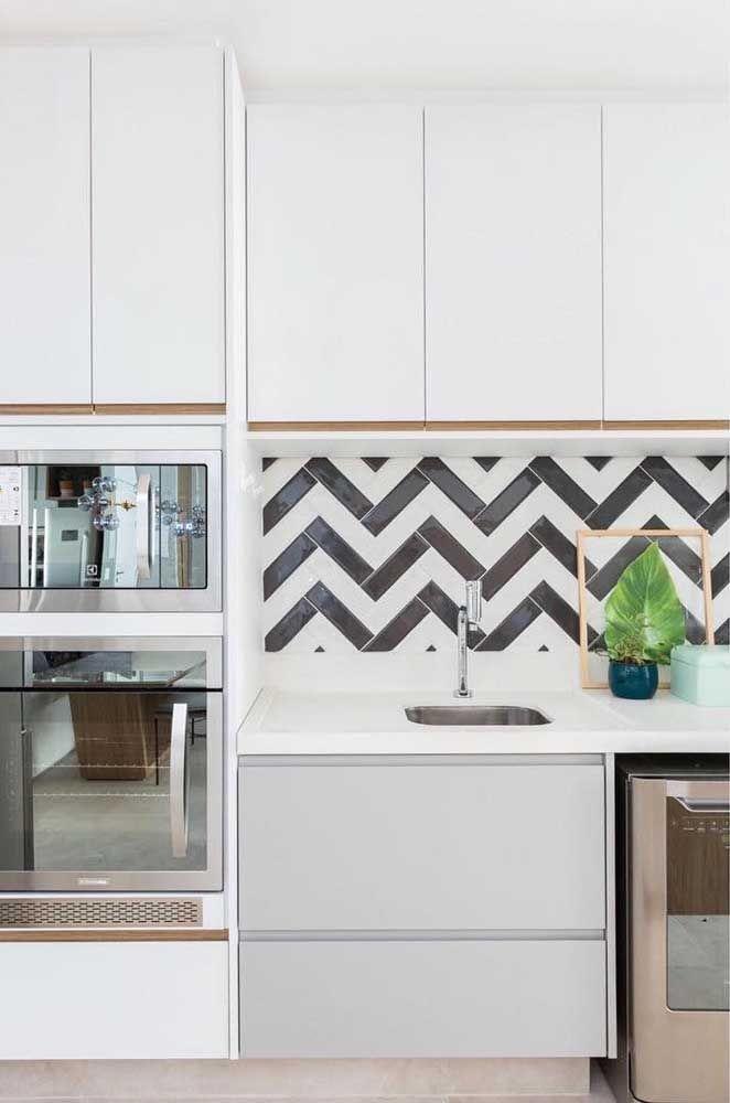 Para completar o visual da cozinha planejada, um revestimento Chevron na parede