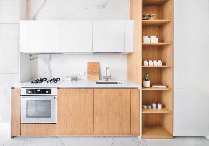 A combinação apaixonante entre o branco e a madeira clara; o revestimento de mármore completa a proposta dessa cozinha