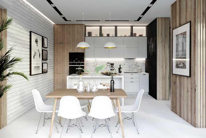 A ilha central ajuda a delimitar a área entre a sala de jantar e a cozinha