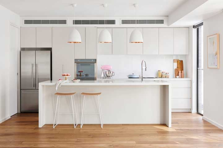 Cozinha planejada branca com detalhes em dourado