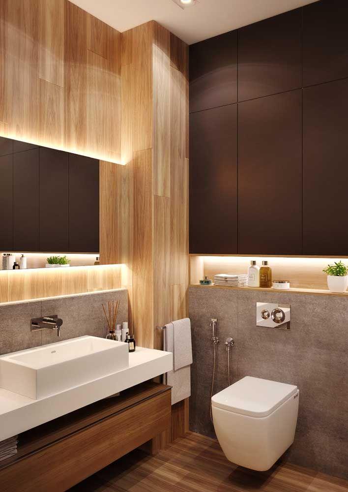 A luz que percorre o espelho valoriza o revestimento de madeira e o nicho decorativo abaixo dele