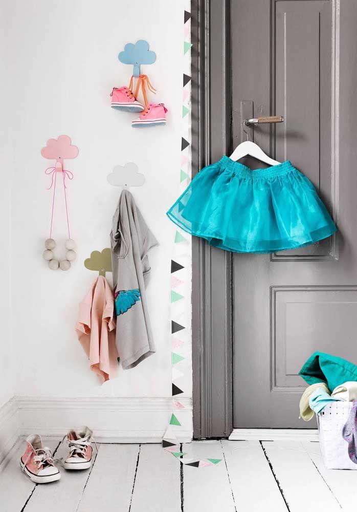 Nuvens delicadas decoram a parede e organizam as roupas das crianças