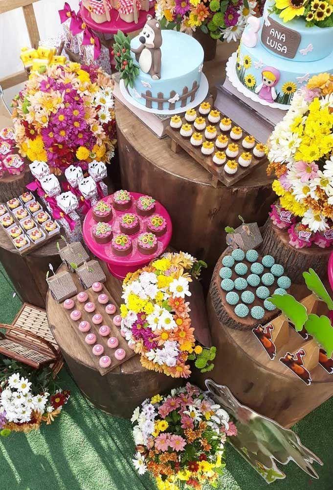 A variedade de flores e os doces coloridos deixam a mesa da festa muito mais harmoniosa