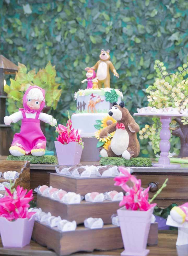 Use os bonecos da Masha e o urso tanto no topo do bolo quanto na decoração da mesa