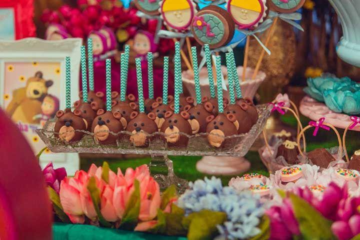 A mesa com decoração da Masha e o Urso precisa ser repleta de flores, doces e itens bem coloridos