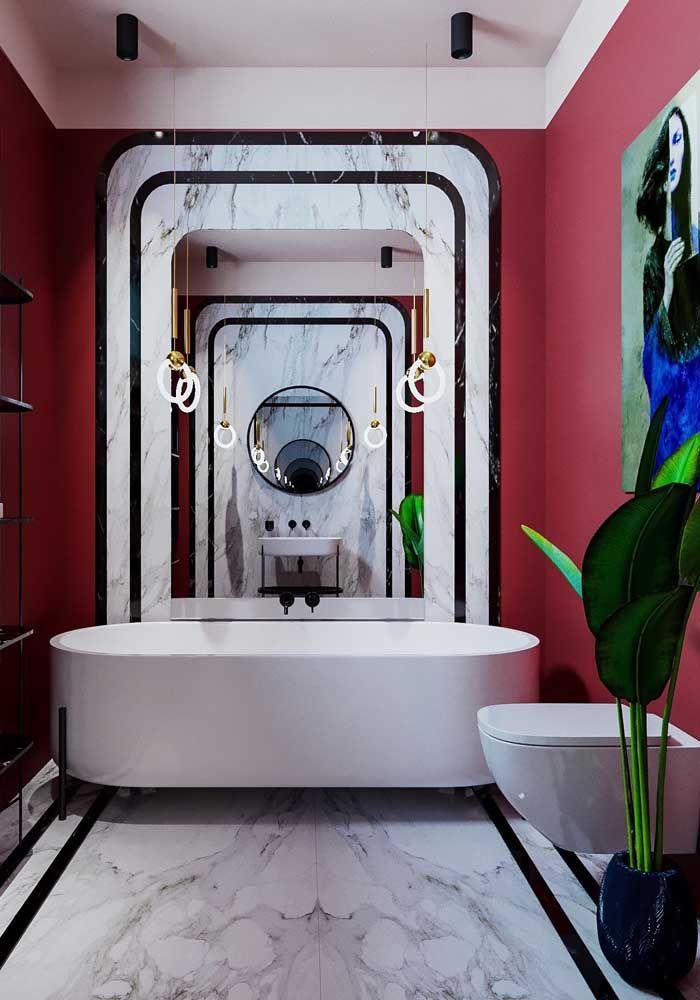 Quer uma decor de arrasar no banheiro? Experimente essa: paredes vermelhas, piso de mármore branco, espelho e detalhes em preto e dourado; o vaso de planta também é importante