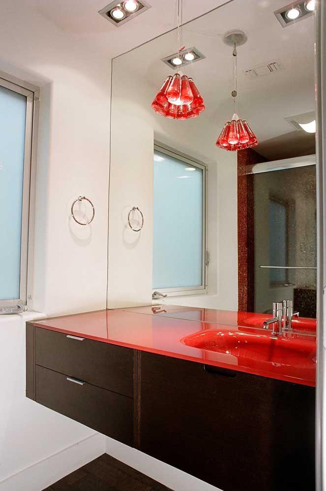 Uma bancada vermelha glamourosa; a luminária completa o visual
