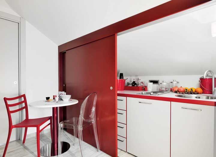 Nessa casa, a cozinha fica escondida por trás de uma sofisticada porta de correr vermelha