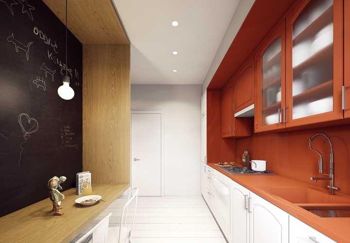 Para acabar com a predominância branca nessa cozinha, a opção foi apostar em um tom de armário vermelho coral