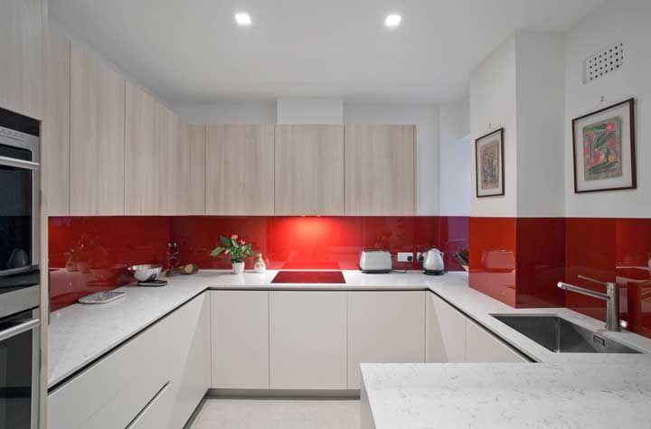 Nessa cozinha, o revestimento que percorre a bancada da pia é todo vermelho, contrastando com os tons claros e neutros da base da decor