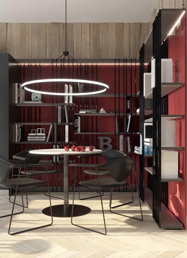 O preto e o vermelho formam uma combinação marcante e estilosa, já as peças de madeira na parede evocam uma atmosfera aconchegante