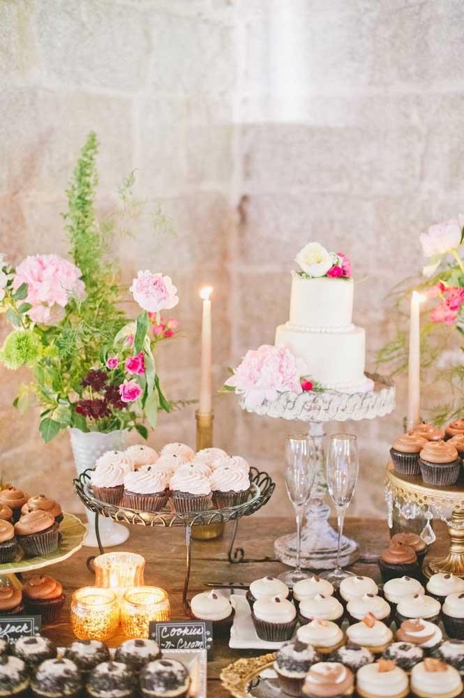 Flores e velas dão o toque final dessa mesa de doces de casamento