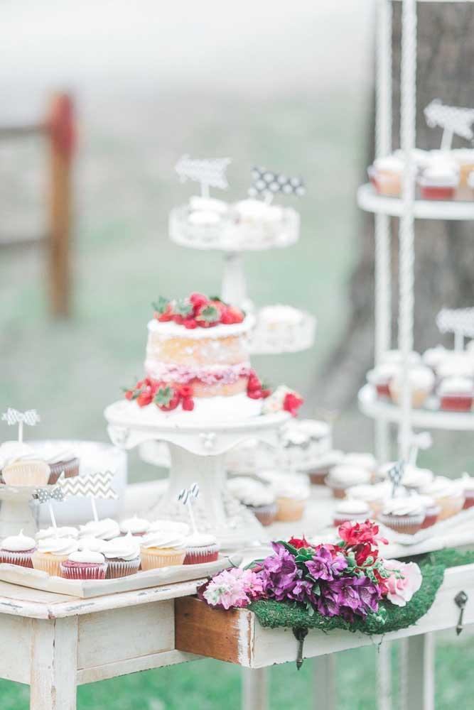 Mesa de guloseimas com toque provençal, repare que o estilo desgastado do móvel se reproduz no efeito espatulado do bolo